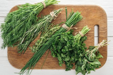 Photo for Top view of parsley, rosemary, dill, green onion, basil and thyme on wooden chopping board - Royalty Free Image