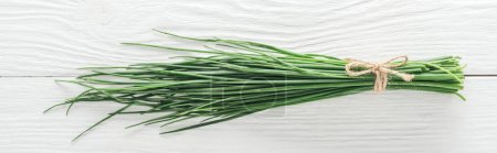 top view of fresh green onion on white wooden table, panoramic shot