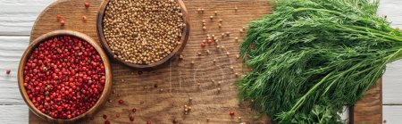 Photo for Panoramic shot of coriander and pink peppercorn in bowls near green dill on wooden chopping board - Royalty Free Image