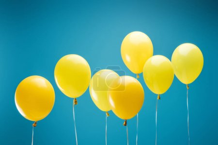 Photo for Bright party yellow balloons on blue background - Royalty Free Image