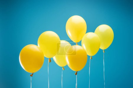 Photo for Bright colorful yellow balloons on blue background - Royalty Free Image