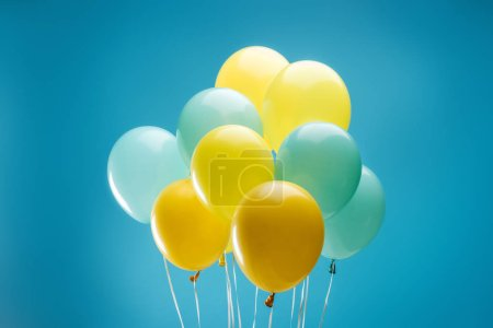 Photo for Bright colorful yellow and blue balloons on blue background - Royalty Free Image