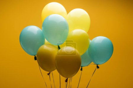 Photo pour Bright decorative blue and yellow balloons on yellow background - image libre de droit