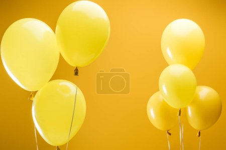 Foto de Festive bright minimalistic balloons on yellow background - Imagen libre de derechos
