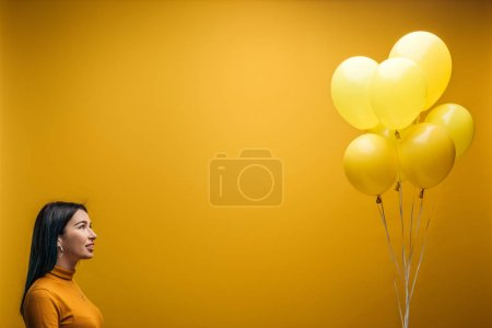 Photo for Smiling girl holding festive minimalistic balloons on yellow background - Royalty Free Image