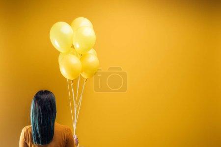 Photo pour Vue arrière de femme retenant les ballons lumineux festifs sur le fond jaune - image libre de droit