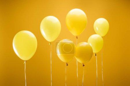 Photo pour Ballons minimalistes lumineux festifs sur le fond jaune - image libre de droit