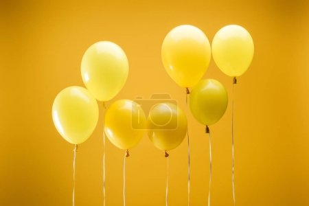 Foto de Bright minimalistic decorative balloons on yellow background - Imagen libre de derechos