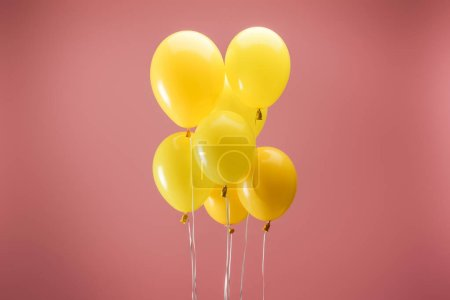 Foto de Yellow festive balloons on pink background, party decoration - Imagen libre de derechos