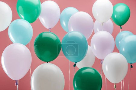 Photo for Bright green, white and blue party decorative balloons on pink background - Royalty Free Image
