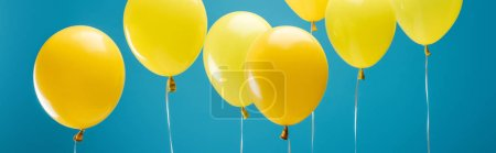Photo for Bright party yellow balloons on blue background, panoramic shot - Royalty Free Image