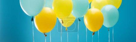 Photo pour Ballons jaunes et bleus colorés sur le fond bleu, projectile panoramique - image libre de droit
