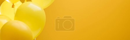 colorful minimalistic decorative balloons on yellow background, panoramic shot