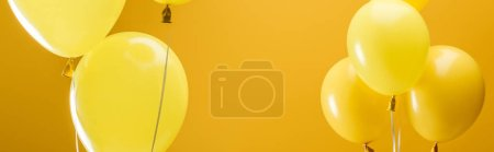 festive bright minimalistic balloons on yellow background, panoramic shot