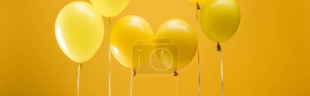 Photo for Party bright minimalistic balloons on yellow background, panoramic shot - Royalty Free Image