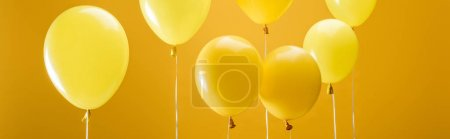 Photo for Party minimalistic balloons on yellow background, panoramic shot - Royalty Free Image