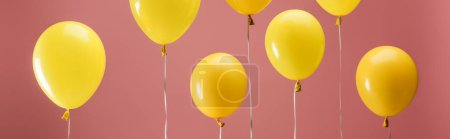 Foto de Yellow bright balloons on pink background, party decoration, panoramic shot - Imagen libre de derechos