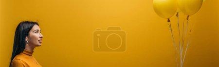 Photo pour Fille de sourire retenant les ballons minimalistes festifs sur le fond jaune, projectile panoramique - image libre de droit