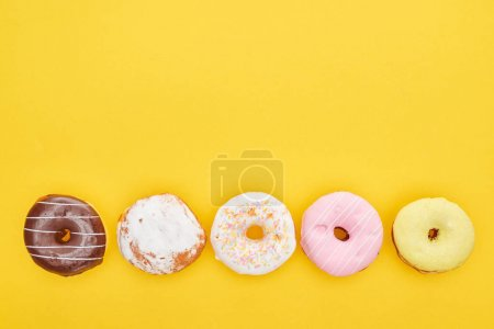 Photo for Top view of tasty glazed doughnuts on bright yellow background - Royalty Free Image