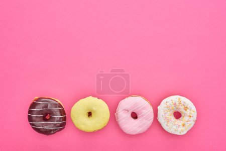 Photo for Top view of tasty glazed doughnuts on bright pink background with copy space - Royalty Free Image