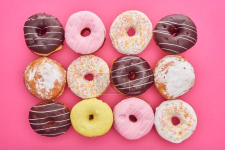 Photo for Top view of tasty round glazed doughnuts on bright pink background - Royalty Free Image