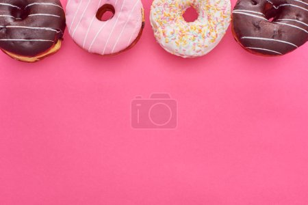 Photo for Top view of delicious glazed doughnuts on bright pink background with copy space - Royalty Free Image