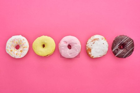 Photo for Flat lay with tasty glazed doughnuts on bright pink background - Royalty Free Image