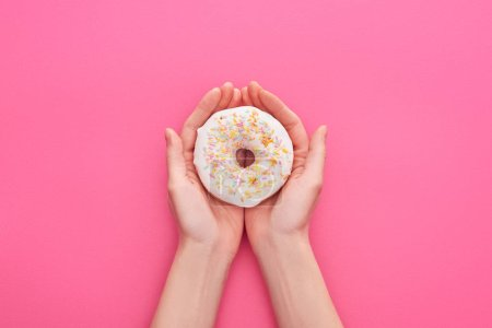 Photo for Partial view of woman holding white glazed doughnuts with sprinkles on pink background - Royalty Free Image
