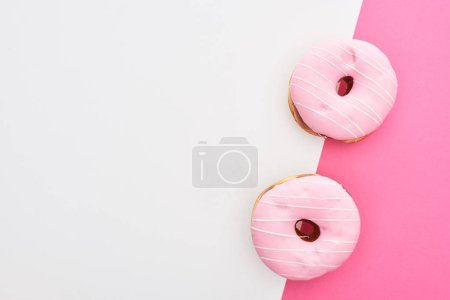 top view of glazed pink doughnuts on white and pink background with copy space