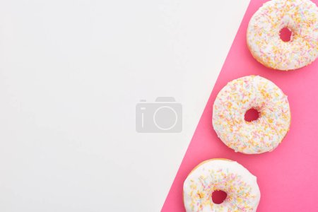 Photo pour Vue supérieure des beignets blancs glacés avec des arrosages sur le fond blanc et rose avec l'espace de copie - image libre de droit