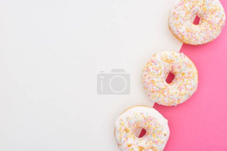 Photo for Top view of tasty glazed doughnuts on white and pink background - Royalty Free Image