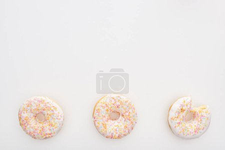 Photo for Top view of sweet whole doughnuts with sprinkles near bitten one on white background - Royalty Free Image