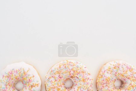 Photo for Top view of white glazed doughnuts with sprinkles on white background - Royalty Free Image