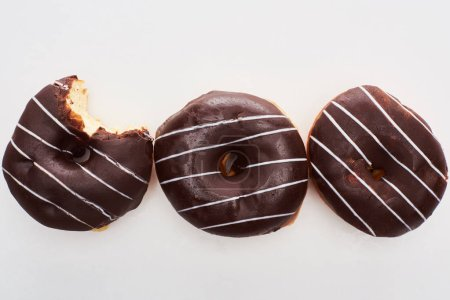 Photo for Top view of chocolate tasty glazed doughnuts on white background - Royalty Free Image