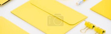 Foto de Toma panorámica de un sobre amarillo, lápiz y clips de papel sobre fondo blanco - Imagen libre de derechos