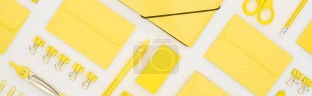 Photo for Panoramic shot of yellow pen, pencils, paper clips, eraser, stickers, envelopes, stickers, folder, scissors and compasses isolated on white - Royalty Free Image
