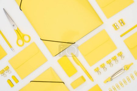 Photo for Top view of yellow pen, pencils, paper clips, eraser, stickers, envelopes, stickers, folders, scissors, pencil sharpeners and compasses isolated on white - Royalty Free Image