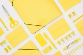 """Постер, картина, фотообои """"top view of yellow pen, pencils, paper clips, eraser, stickers, envelopes, stickers, folders, scissors, pencil sharpeners and compasses isolated on white"""""""