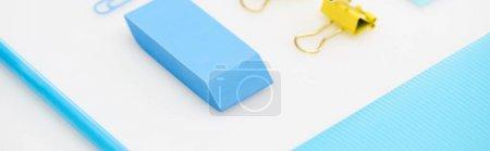 Foto de Toma panorámica de clip de papel azul, borrador, lápiz, carpeta y clips de papel amarillos aislados en blanco - Imagen libre de derechos