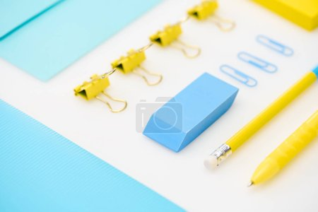 Photo for Flat lay of blue eraser, paper clips, folder, envelope, yellow pen, pencil, stickers in white background - Royalty Free Image