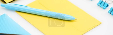 panoramic shot of blue folder, paper clips and pen on yellow envelope on white background