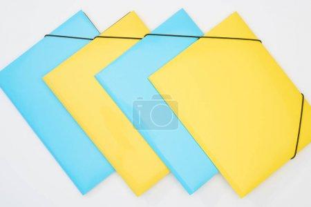 Flache Lage aus gelben und blauen Ordnern auf weißem Hintergrund
