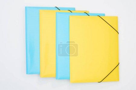 Flache Lage aus gelben und blauen Ordnern isoliert auf weiß
