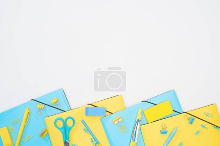 Photo for Top view of blue and yellow stationery isolated on white - Royalty Free Image