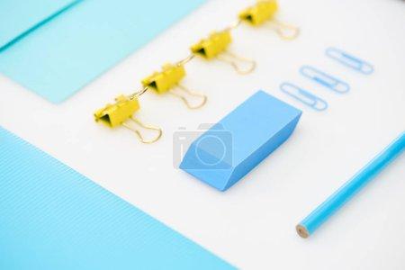 Foto de Flat Lay de clips de papel azul, borrador, carpeta, lápiz, sobre y clips de papel amarillos - Imagen libre de derechos