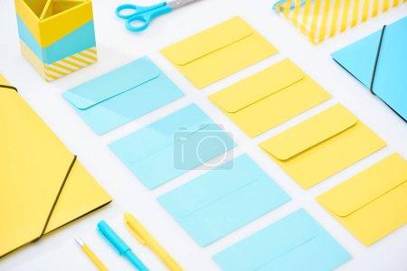 Foto de Plano de sobres azules y amarillos y otros artículos de papelería sobre fondo blanco - Imagen libre de derechos