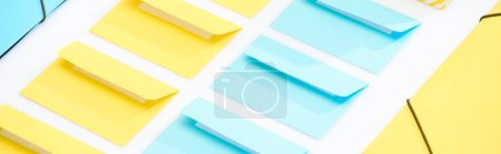panoramic shot of yellow and blue folders and opened envelopes on white background