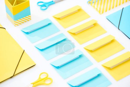 Photo for Flat lay of colourful envelopes, scissors, folders, pencil case and pencil box on white background - Royalty Free Image