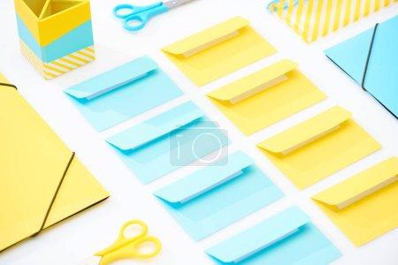Flache Lage aus bunten Umschlägen, Scheren, Ordnern, Mäppchen und Bleistiftschachtel auf weißem Hintergrund