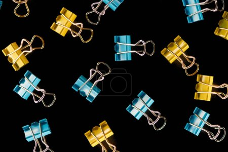 Photo for Top view of colorful scattered yellow, orange and blue paper clips isolated on black - Royalty Free Image